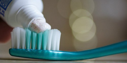 toothpaste being applied on toothbrush
