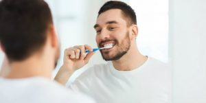 a man is brushing his teeth