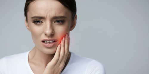 a woman feels pain due to toothache