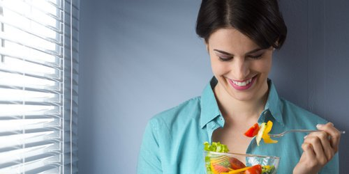 a woman teasing her salad before eating it