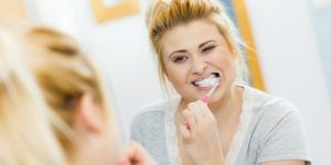 a woman carefully brush her teeth