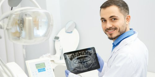 A doctor show his patient's teeth image on a routine check up