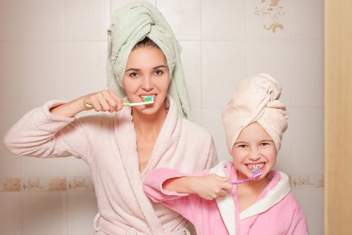 mother and child are brushing their teeth