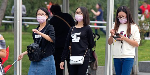 3 women wearing face mask avoiding air pollution walking on the street