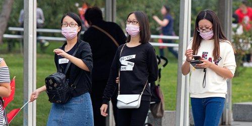 3 women wearing face mask avoiding air pollution walking on the street