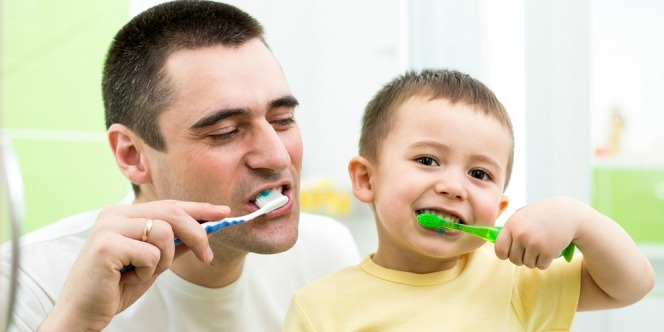 the father is inviting his son to brush his teeth